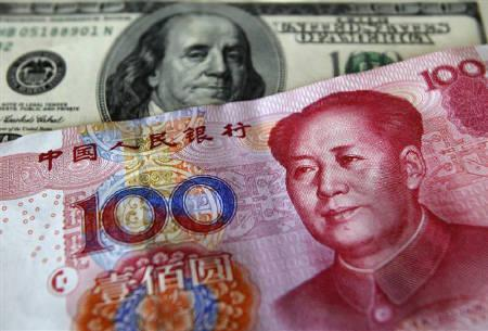 A yuan banknote is displayed next to a U.S. dollar banknote (back) for the photographer at a money changer inside the Taoyuan International Airport March 18, 2010. REUTERS/Nicky Loh/Files