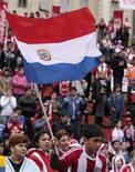 <p>Болельщики сборной Парагвая празднуют победу команды в матче против Словакии, 20 июня 2010 года. Сборная Парагвая сыграет против сборной Новой Зеландии в финальном матче группы F на чемпионате мира по футболу в четверг. REUTERS/Jorge Adorno</p>