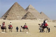 <p>Foreign tourists ride camels at the Pyramids in Cairo February 12, 2009. REUTERS/Tarek Mostafa</p>