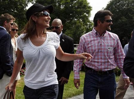 Former Governor of Alaska Sarah Palin and her husband Todd (R) leave the paddock at the 142nd Belmont Stakes, the final leg of racing's Triple Crown, at Belmont Park in Elmont, New York June 5, 2010. REUTERS/Jessica Rinaldi