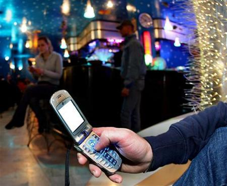 A man keys in a message onto a mobile phone in a Milan bar March 3, 2006. REUTERS/Daniele LA Monaca