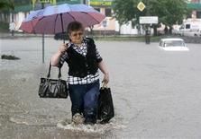 <p>Женщина идет по затопленной улице Тернополя, 3 июня 2010 года. Вызванное обильными осадками наводнение в западных регионах Украины привело к гибели двух человек и остановке железнодорожного сообщения с соседней Румынией из-за разрушения 11 мостов, сообщило Министерство по чрезвычайным ситуациям Украины. REUTERS/Viktor Gurniak</p>