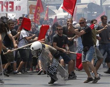 Protesters beat a riot policeman during a rally against government austerity measures in Athens June 29, 2010. REUTERS/John Kolesidis