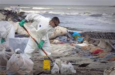 <p>Un contratista de BP remueve crudo de una playa en Port Fourchon, EEUU, mayo 23 2010. La perforación de un pozo de alivio para desvia el derrame de crudo de BP en el Golfo de México está aún a semanas de concluir, dijo el miércoles un alto funcionario estadounidense, con el primer huracán de la temporada afectando las tareas de limpieza. REUTERS/Lee Celano/Files</p>