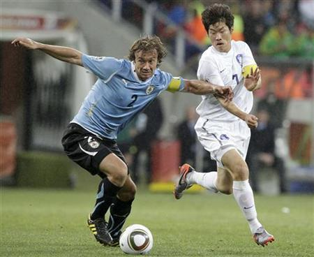 Uruguay's Diego Lugano (L) fights for the ball against South Korea's Park Ji-sung during the 2010 World Cup second round match in Port Elizabeth June 26, 2010. REUTERS/Denis Balibouse
