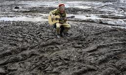 <p>Молодой человек играет на гитаре, сидя в грязи в поле в поселке Булгаково, 13 июня 2009 года. Девять из десяти жителей России предпочли бы дыму отечества высокий уровень жизни Европы или США, имей они возможность получать стабильный доход от удаленной работы, свидетельствуют данные июньского опроса интернет-компании Mail.ru и веб-сайта Free-lance.ru. REUTERS/Denis Sinyakov</p>
