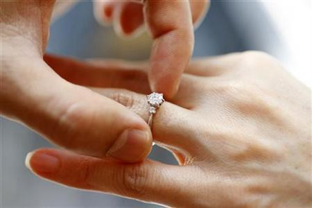 A man puts an engagement ring on a woman's finger during a photo opportunity at a jewellery store in Tokyo June 2, 2009. REUTERS/Yuriko Nakao