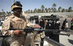 <p>Солдат следит за шествием паломников в Ираке, 7 июля 2010 года. Как минимум шесть человек погибли и еще 37 получили ранения в результате атаки на религиозных паломников в северной части Багдада во вторник, сообщила полиция. REUTERS/Saad Shalash</p>