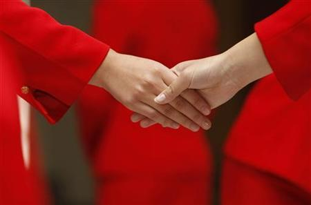 Students shake hands during etiquette training at a vocational school in Beijing October 25, 2007. REUTERS/Jason Lee