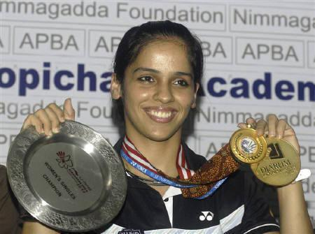 Badminton player Saina Nehwal holds her medals from the Singapore Open Series, India Open Grand Prix and Djarum Indonesia Open Super Series tournaments during a news conference in Hyderabad June 29, 2010. REUTERS/Krishnendu Halder/Files