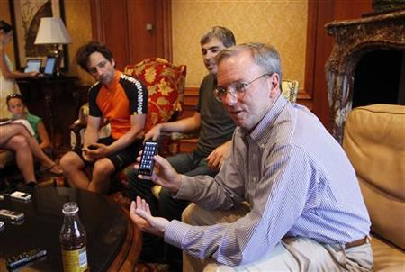 Google Chairman and Chief Executive Eric Schmidt (R) holds a Droid X smartphone, as co-founders Sergey Brin (L) and Larry Page watch, while he talks to reporters at the Sun Valley Inn in Sun Valley, Idaho July 8, 2010. REUTERS/Mario Anzuoni