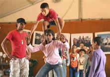 <p>Children practice an acrobatic figure as others watch during a workshop at the Nomadic Theatre in Rabat July 8, 2010. REUTERS/Eve Coulon-Pfeiffer</p>