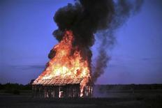 <p>Polish performance artist Rafal Betlejemski burns down a barn in the village of Zawady, near Tomaszow Mazowiecki, central Poland July 11, 2010. Betlejemski burnt the barn to commemorate the 69th anniversary of the Jedwabne pogrom in which, according to the investigation of the Polish Institute of National Remembrance Poles burned alive more then 300 Jews locked in a barn. REUTERS/Agencja Gazeta/Filip Klimaszewski</p>