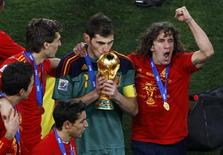 <p>Spain's goalkeeper Iker Casillas kisses the World Cup trophy as team mate Carles Puyol (R) celebrates after their final match victory over Netherlands at the 2010 World Cup at Soccer City stadium in Johannesburg July 11, 2010. REUTERS/David Gray</p>