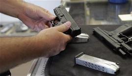 <p>Мужчина проверяет пистолет в одном из магазинов штата Иллинойс, 26 июня 2010 года. Бывший сотрудник компании Emcore Corp убил двух человек из огнестрельного оружия в штаб-квартире фирмы в Альбукерке в понедельник, после чего застрелился сам, сообщила полиция. REUTERS/Frank Polich/Files</p>