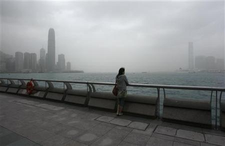 A girl rests on the waterfront facing Hong Kong's Victoria Harbour March 22, 2010. REUTERS/Bobby Yip