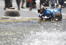 <p>A boy dunks his face into a fountain to cool down during a hot summer day in St. Peter's Square, Rome July 16, 2010 REUTERS/Alessandro Bianchi</p>