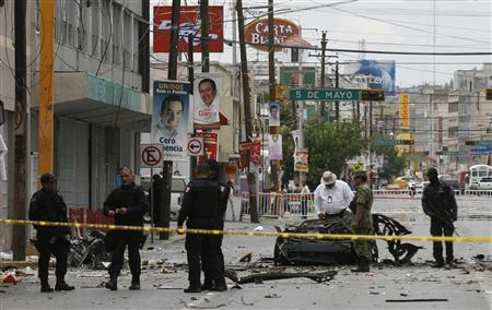 Federal policemen and explosive experts work at the site of a car bomb attack in Ciudad Juarez July 16, 2010. A Mexican drug cartel was responsible for a cell phone-detonated car bomb that killed four people in a city on the U.S. border, state security forces said on Friday. In the first attack of its kind during Mexico's drug war, the explosion tore through a major intersection in Ciudad Juarez across the border from El Paso, Texas, late on Thursday. REUTERS/Alejandro Bringas