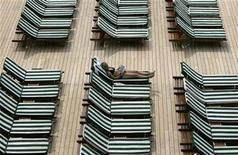 <p>A woman sunbathes on the deck of an ocean liner in a file photo. REUTERS/Paul Yeung</p>