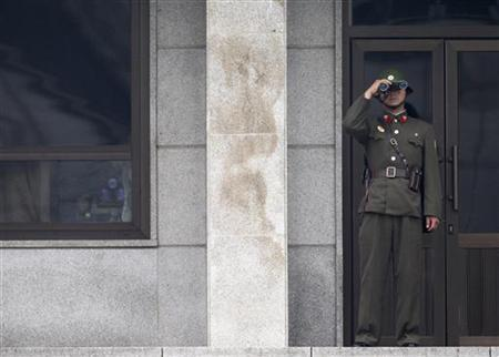 A North Korean soldier looks at the south through a pair of binoculars as he stands guard at the south from the north side of the truce village of Panmunjom in the demilitarized zone separating the two Koreas in Paju, about 55 km (34 miles) north of Seoul, June 30, 2010. REUTERS/Jo Yong-Hak