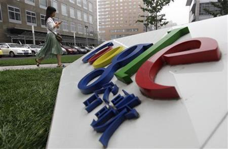 An employee walks past the logo of Google in front of its former headquarters in Beijing in this July 12, 2010 file photo. REUTERS/Jason Lee