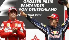 """<p>Fernando Alonso (dir) comemora no pódio ao lado do colega de equipe Felipe Massa (esq) depois de vender o GP da Alemanha. A Ferrari foi multada em 100 mil dólares neste domingo por ter dado """"ordens ilegais"""" permitindo ao brasileiro Massa a ultrapassagem do espanhol Alonso. 25/07/2010 REUTERS/Kai Pfaffenbach</p>"""
