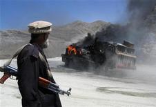 """<p>Сотрудник службы безопасности Пакистана стоит рядом с горящим автомобилем в одной из провинций, граничащих с Афганистаном, 19 мая 2010 года. Пакистан активно сотрудничал с боевиками из движения """"Талибан"""", одновременно получая финансовую помощь от США, свидетельствуют опубликованные в понедельник американские военные документы. REUTERS/Saeed Ali Achakzai</p>"""