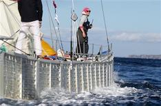 <p>Crew member Jo Royle watches from the deck of the 60-foot-long Plastiki catamaran, built from more than 11,000 reclaimed bottles and other recycled plastic and waste products, as it is towed through Sydney Harbour at the end of its Trans-Pacific crossing July 26, 2010. REUTERS/Daniel Munoz</p>