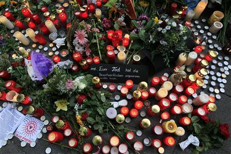 A condolence card for the victims of a stampede is placed amid a sea of candles in Duisburg July 25, 2010. REUTERS/Wolfgang Rattay