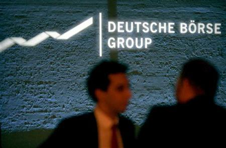 Guests stand in front of a sign for Deutsche Boerse Group, which owns the German stock exchange, projected on a wall during their annual reception at the Tate Modern gallery in London, January 20, 2005.