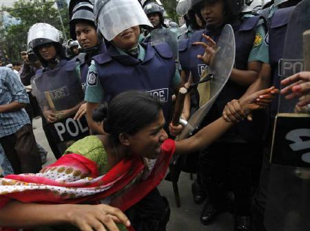 Police officers try to arrest a garment worker during a protest in Dhaka July 30, 2010. Thousands of Bangladeshi garment workers took to the streets, burning cars and blocking traffic in Dhaka to protest against a government-announced wage hike that fell far short of their demands. REUTERS/Andrew Biraj