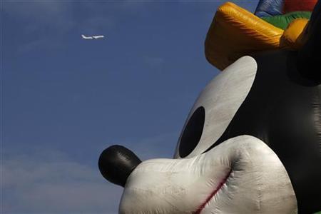 A plane flies past a musical parade at Hong Kong Disneyland November 4, 2009. REUTERS/Tyrone Siu