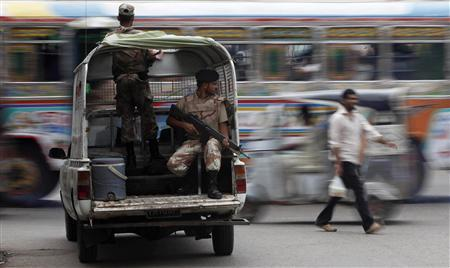 A man walks past a moving bus as Rangers keep guard at an intersection in Karachi on August 4, 2010. REUTERS/Akhtar Soomro