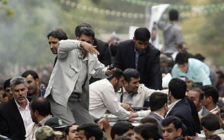 EDITORS' NOTE:  Reuters and other foreign media are subject to Iranian restrictions on their ability to film or take pictures in Tehran. Bodyguards react after the sound of an explosion behind the entourage of Iranian President Mahmoud Ahmadinejad (C) as he is welcomed to Hamadan, 336 kilometres southwest of Tehran, August 4, 2010. REUTERS/STR