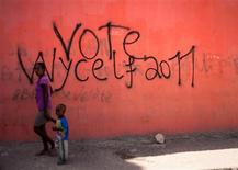 <p>Una mujer y un niño pasan frente a un mural en apoyo de la candidatura presidencial del cantante Wyclef Jean en las calles de Croix-des-Bouquets, Haití, ago 5 2010. Jean se registró el jueves como candidato presidencial para las elecciones de noviembre en Haití. El cantautor presentó los papeles a las autoridades electorales para ser candidato del partido Viv Ansanm. REUTERS/Allison Shelley</p>