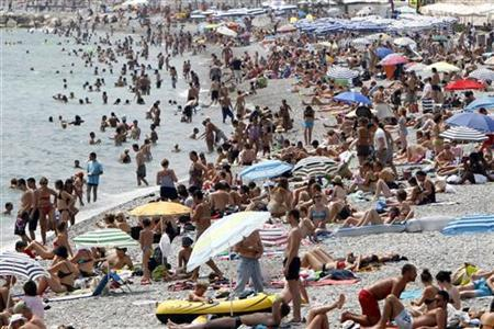 Holidaymakers and tourists sunbathe on the beach on a hot summer day in Nice, south eastern France, July 9, 2010. REUTERS/Sebastien Nogier