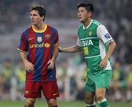 <p>Lionel Messi do Barcelona(esq) ao lado de Lu Jiang do Beijing Guoan em amistoso em Pequim. O time reserva do Barcelona, reforçado com participações rápidas de Lionel Messi e Zlatan Ibrahimovic, venceram a partida por 3 x 0. 08/08/2010 REUTERS/Petar Kujundzic</p>