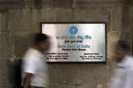People walk in front of a signboard displayed at the head office of State Bank of India in Mumbai November 9, 2009. REUTERS/Arko Datta