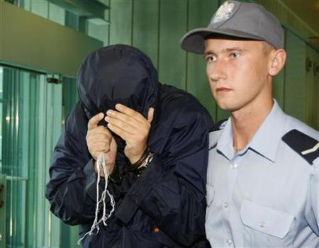 A man using the name Uri Brodsky hides his face under a hood as he is escorted by police in Warsaw's Court of Appeal August 5, 2010. REUTERS/Kacper Pempel