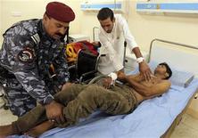 <p>Военный и врач укладывают на койку раненого в результате взрыва экстремиста-смертника на территории армейского вербовочного центра в Багдаде 17 августа 2010 года. Сорок семь человек погибли и 77 получили ранения в результате взрыва экстремиста-смертника на территории армейского вербовочного центра в Багдаде, сообщил заместитель министра здравоохранения Ирака Хамис аль-Саад. REUTERS/Mohammed Ameen</p>