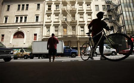 A man carries a bicycle in front of a lower Manhattan building that will possibly house the Cordoba Initiative Mosque and Cultural Center in New York August 17, 2010. REUTERS/Lucas Jackson