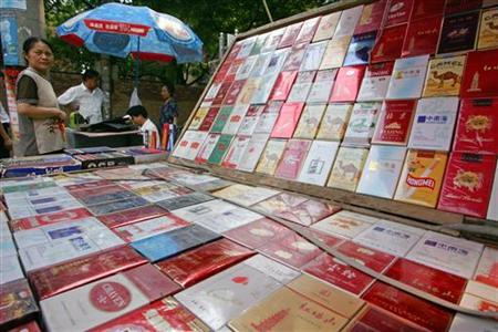 A cigarette vendor waits for customers at a street corner in Beijing August 29, 2005. REUTERS/Claro Cortes