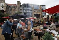 <p>A man serves grilled food in the backyard of the Tacheles alternative art centre in Berlin, August 7, 2010. REUTERS/Thomas Peter</p>