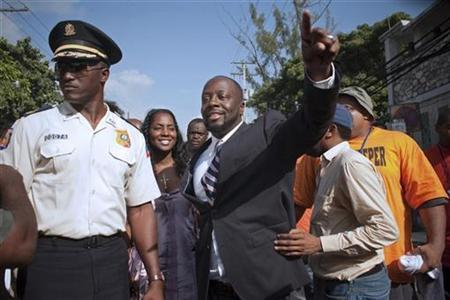 Hip-hop star Wyclef Jean greets the crowd before officially registering as a presidential candidate at an office in the Delmas neighborhood of Port-au-Prince August 5, 2010. REUTERS/Allison Shelley