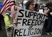 <p>A man holds a sign during a rally held to support a proposed Muslim cultural center and mosque near the World Trade Center site in New York August 22, 2010. REUTERS/Jessica Rinaldi</p>