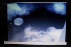 <p>A computer screen shows a recorded image of one of the 33 miners trapped in a deep underground copper and gold mine at Copiapo, 725 km (450 miles) north of Santiago, August 23, 2010. REUTERS/Ivan Alvarado</p>