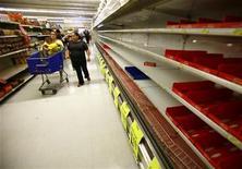 <p>Покупатели идут вдоль пустых прилавков бакалейного магазина Food Town в Хьюстоне, 17 сентября 2008 года. Аномальная засуха в России спровоцировала на спекуляции производителей продуктов питания, при этом наиболее серьезно пострадали молочные продукты и крупы, где дефицит и серьезный рост цен неизбежен, заявили представители российских розничных сетей на пресс-конференции в понедельник. REUTERS/Richard Carson</p>
