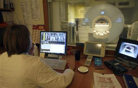 A radiologist studies an image from a magnetic resonance imaging (MRI) scanner at the Ambroise Pare hospital in Marseille, southern France, April 8, 2008. REUTERS/Jean-Paul Pelissier