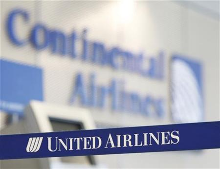 A Continental Airlines logo looms over a United Airlines logo in Chicago's O'Hare International Airport May 3, 2010. REUTERS/John Gress