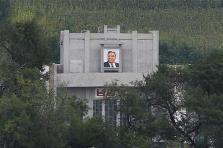 A portrait of former North Korean leader and founder Kim Il-Sung is seen from across the Tumen river at a border crossing with China's northern Jilin province August 29, 2010. REUTERS/Aly Song